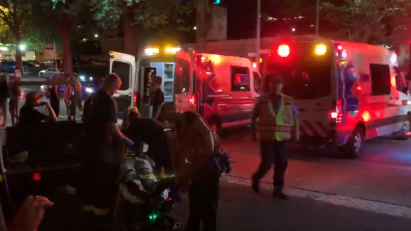 Paramedics transfer injured festival-goers following Bumbershoot barricade collapse